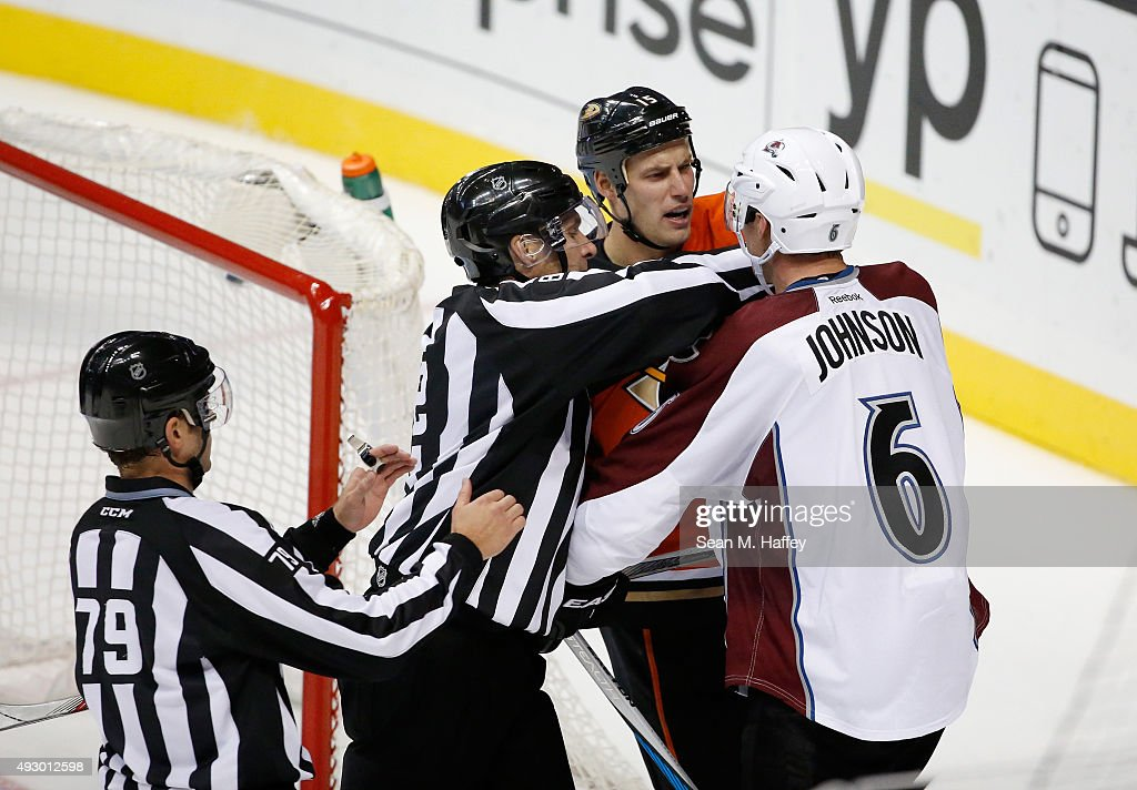 Linesman Kiel Murchison #79, linesman Ryan Galloway restrain Erik Johnson #6 of the Colorado Avalanche and Ryan Getzlaf #15 of the Anaheim Ducks during the third period of a game at Honda Center on October 16, 2015 in Anaheim, California.