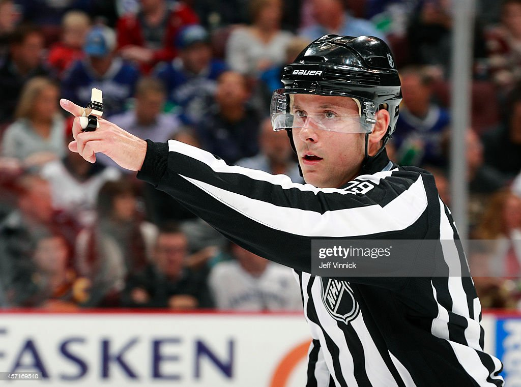 Linesman Kiel Murchison makes a call during the NHL game between the Vancouver Canucks and the Edmonton Oilers at Rogers Arena October 11, 2014 in Vancouver, British Columbia, Canada. Vancouver won 5-4 in a shootout.