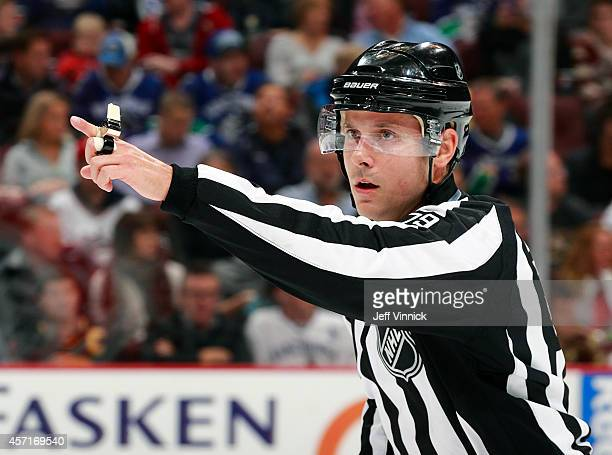 Linesman Kiel Murchison makes a call during the NHL game between the Vancouver Canucks and the Edmonton Oilers at Rogers Arena October 11 2014 in...
