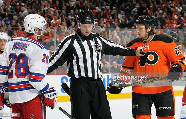 Linesman Kiel Murchison separates Ryan White of the Philadelphia Flyers from Dominic Moore of the New York Rangers following a scrum on February 6...