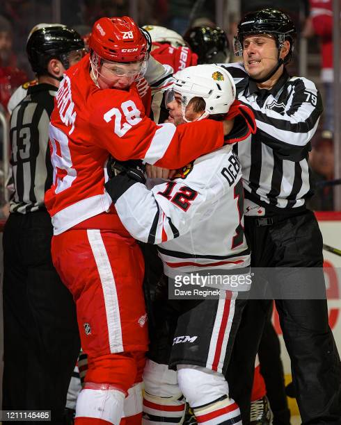 Linesman Kiel Murchison tries to separate Gustav Lindstrom of the Detroit Red Wings and Alex DeBrincat of the Chicago Blackhawks during an NHL game...