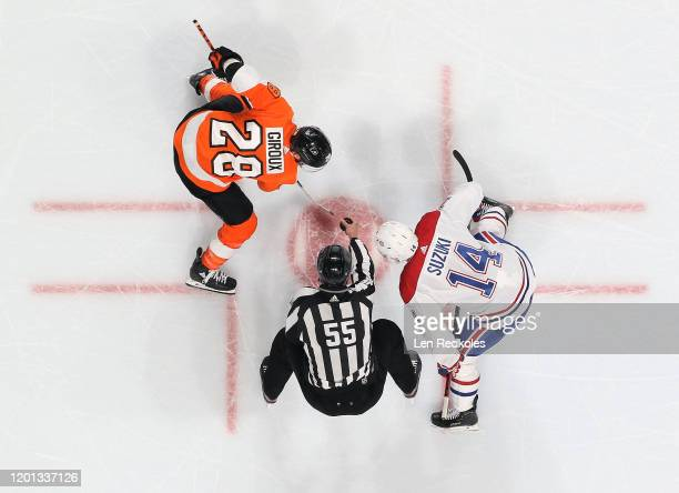 Linesman Kyle Flemington prepares to drop the puck on a face-off between Claude Giroux of the Philadelphia Flyers and Nick Suzuki of the Montreal...