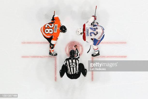 Linesman Kyle Flemington prepares to drop the puck on a face-off between Claude Giroux of the Philadelphia Flyers and Phillip Danault of the Montreal...