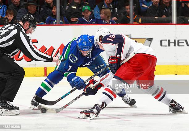 Linesman Lonnie Cameron drops the puck as Linden Vey of the Vancouver Canucks and Ryan Johansen of the Columbus Blue Jackets faceoff during their NHL...
