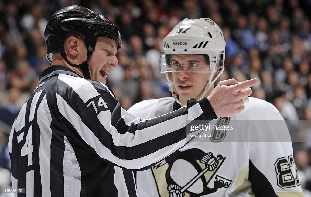 Linesman Lonnie Cameron talks with Sidney Crosby #87 of the Pittsburgh Penguins during a break in NHL game action against the Toronto Maple Leafs March 9, 2013 at the Air Canada Centre in Toronto, Ontario, Canada.