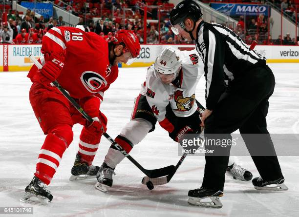 Linesman Mark Shewchyk drops the puck for a faceoff between Jay McClement of the Carolina Hurricanes and JeanGabriel Pageau of the Ottawa Senators...