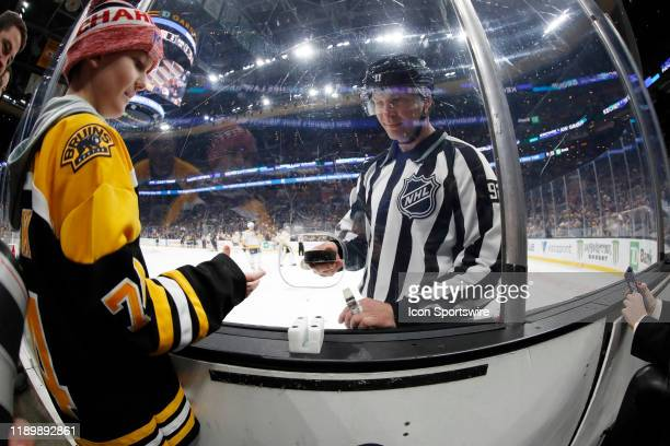 Linesman Mark Shewchyk gives a young fan a game puck during a game between the Boston Bruins and the Nashville Predators on December 21 at TD Garden...