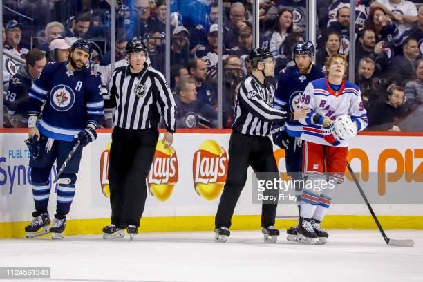 Linesman Matt MacPherson and linesman Travis Gawryletz separate Dustin Byfuglien of the Winnipeg Jets and Vladislav Namestnikov of the New York...