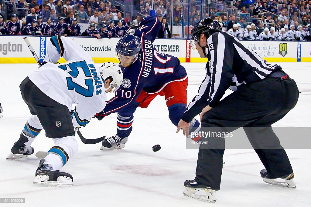 Linesman Matt MacPherson #83 drops the puck for a face-off between Tommy Wingels #57 of the San Jose Sharks and Alexander Wennberg #10 of the Columbus Blue Jackets during the second period on October 15, 2016 at Nationwide Arena in Columbus, Ohio.