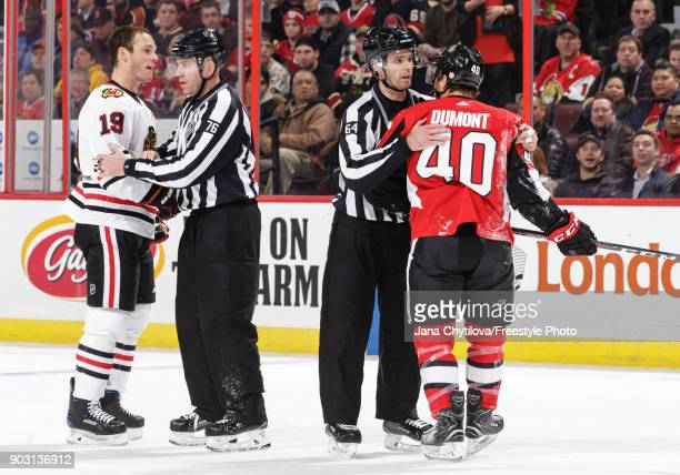 Linesman Michel Cormier and Brandon Gawryletz separate Gabriel Dumont of the Ottawa Senators and Jonathan Toews of the Chicago Blackhawks in the...