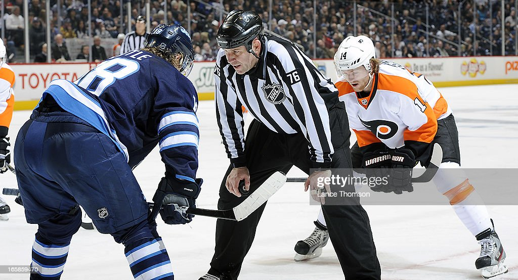 Linesman Michel Cormier #76 has words with Bryan Little #18 of the Winnipeg Jets prior to a third period face-off against Sean Couturier #14 of the Philadelphia Flyers at the MTS Centre on April 6, 2013 in Winnipeg, Manitoba, Canada.