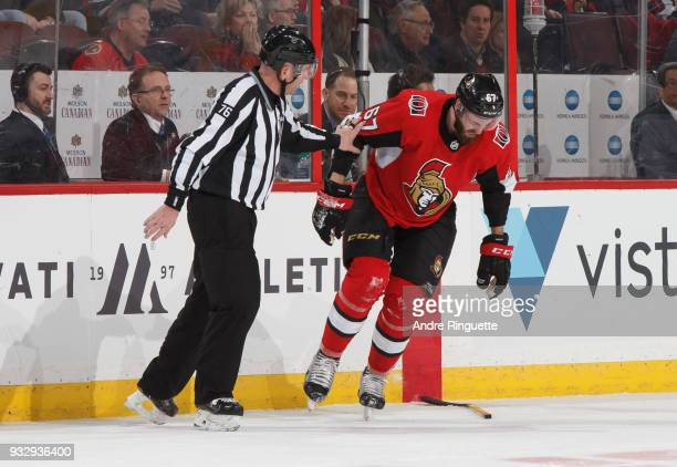 Linesman Michel Cormier looks on as Ben Harpur of the Ottawa Senators grimaces after receiving a high stick to the face during an NHL game against...