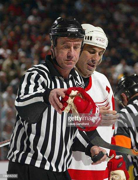 Linesman Pat Dapuzzo grabs the glove of Chris Chelios of the Detroit Red Wings as Chelios looks at his finger during a break in NHL game action...