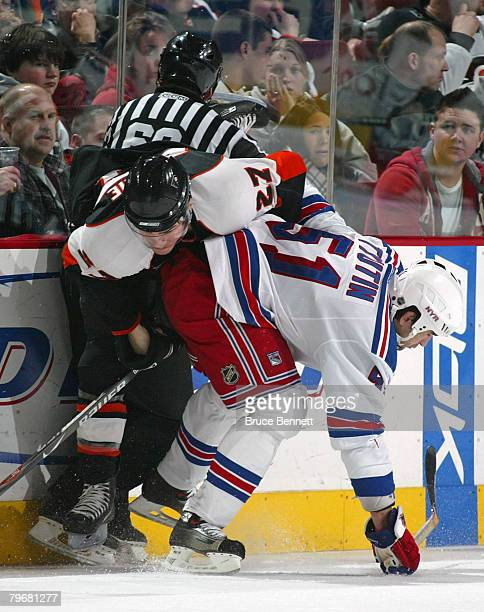 Linesman Pat Dapuzzo is injured by the skate of Steve Downie of the Philadelphia Flyers as he is checked by Fedor Tyutin of the New York Rangers on...