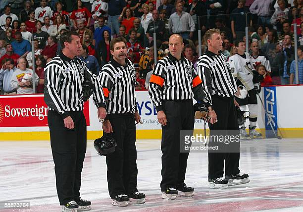 Linesman Pat Dapuzzo referee Bill McCreary referee Craig Spada and linesman Brad Lazarowich line up at center ice prior to start of play between the...
