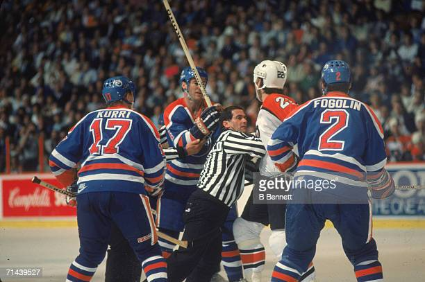Linesman Ray Scapinello breaks up an altercation between Rick Tocchet of the Philadelphia Flyers and Kevin Lowe of the Edmonton Oilers whose...