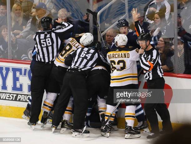 Linesman Ryan Gibbons and Brandon Gawryletz try to separate Winnipeg Jets and Boston Bruins players during a second period scrum at the Bell MTS...