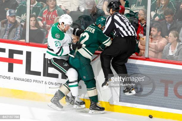 Linesman Ryan Gibbons leaves his feet to avoid the puck and collides with Nino Niederreiter of the Minnesota Wild and Brett Ritchie of the Dallas...