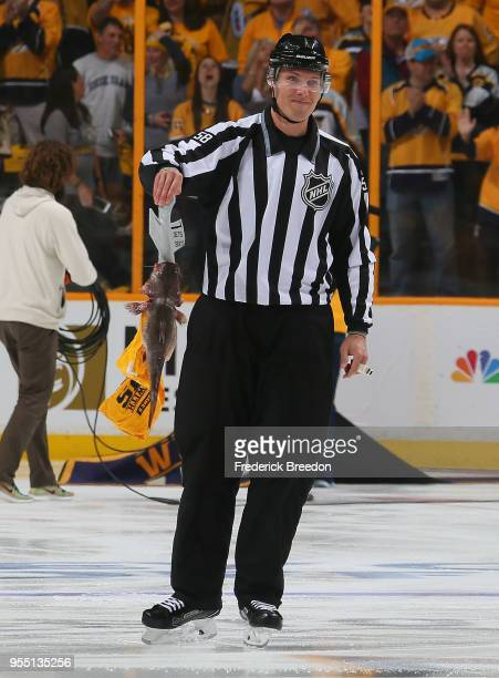 Linesman Ryan Gibbons#58 picks up a catfish prior to a game between the Nashville Predators and the Winnipeg Jets during the first period of Game...