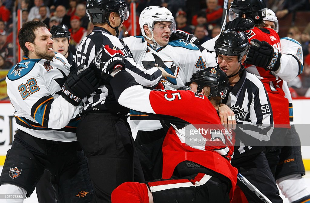 Linesman Scott Cherrey (50) and Steve Barton (59) try to separate Dan Boyle #22 and Marc-Edouard Vlasic #44 of the San Jose Sharks and Chris Neil #25 of the Ottawa Senators from a skirmish caused by a late hit in a game at Scotiabank Place on December 2, 2010 in Ottawa, Ontario, Canada.