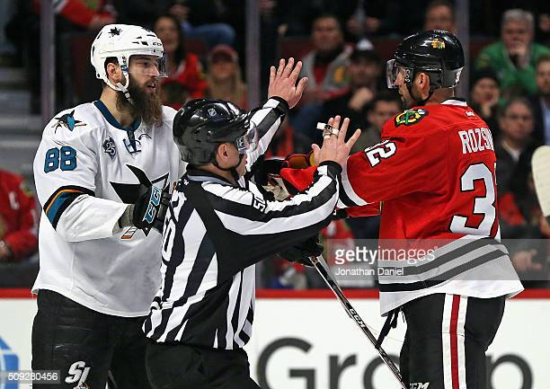 Linesman Scott Cherrey gets in between Brent Burns of the San Jose Sharks and Michal Rozsival of the Chicago Blackhawks at the United Center on...
