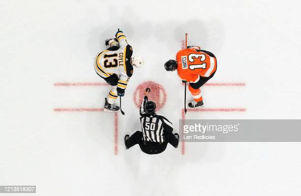 Linesman Scott Cherrey prepares to drop the puck on a face-off between Kevin Hayes of the Philadelphia Flyers and Charlie Coyle of the Boston Bruins...