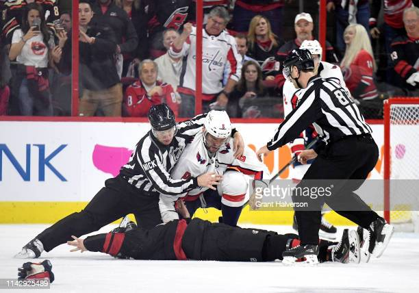 Linesman Scott Cherrey pulls Alex Ovechkin of the Washington Capitals off of Andrei Svechnikov of the Carolina Hurricanes during the first period in...