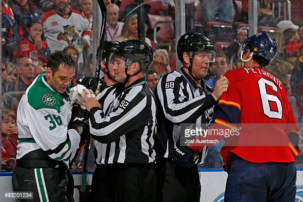Linesman Scott Driscoll and linesman Mark Shewchyk separate Alex Petrovic of the Florida Panthers and Vernon Fiddler of the Dallas Stars after they...
