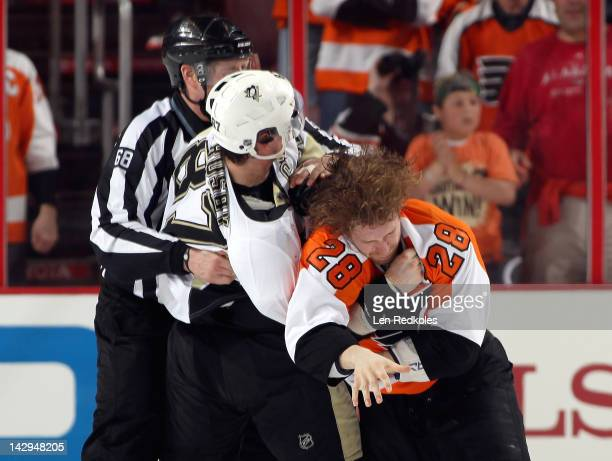 Linesman Scott Driscoll attempts to break up a fight in the first period between Claude Giroux of the Philadelphia Flyers and Sidney Crosby of the...