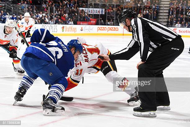 Linesman Scott Driscoll drops the puck between Ben Smith of the Toronto Maple Leafs and Mikael Backlund of the Calgary Flames during game action on...