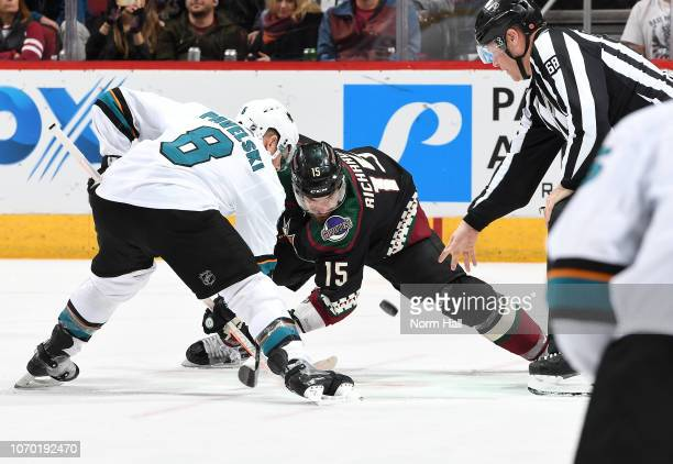 Linesman Scott Driscoll drops the puck for a faceoff between Brad Richardson of the Arizona Coyotes and Joe Pavelski of the San Jose Sharks during...