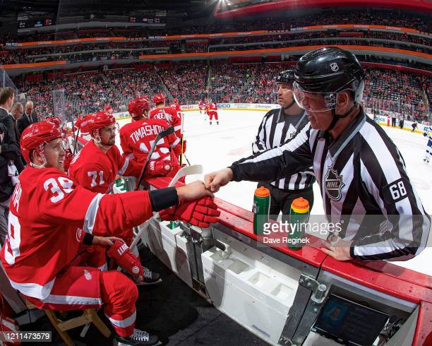 Linesman Scott Driscoll fist bumped by Anthony Mantha of the Detroit Red Wings for his last NHL career game at Little Caesars Arena and his...