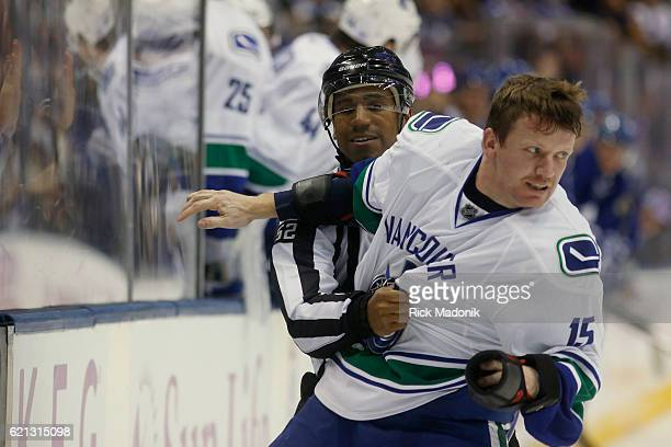 Linesman Shandor Alphonso restrains Vancouver Canucks right wing Derek Dorsett from breaking loose to continue his aggression Dorsett was being sent...