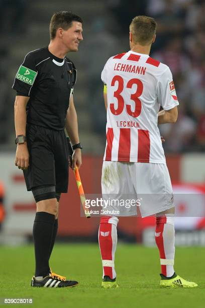 Linesman Stefan Lupp jokes with Matthias Lehmann of Koeln while they wait for the 4th official to come on as new referee during the Bundesliga match...