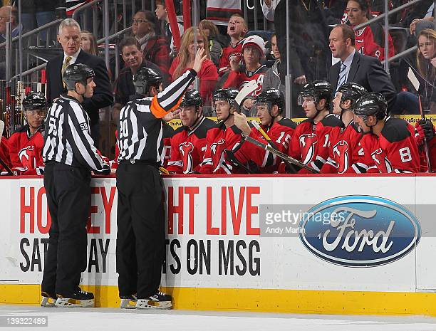 Linesman Steve Barton and referee Tim Peel have a discussion with New Jersey Devils head coach Peter DeBoer during the game against the Anaheim Ducks...