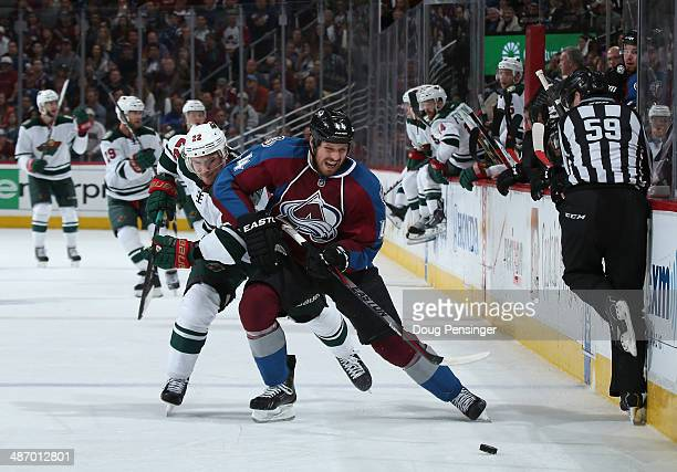 Linesman Steve Barton avoids the action as Ryan Wilson of the Colorado Avalanche controls the puck against Nino Niederreiter of the Minnesota Wild in...