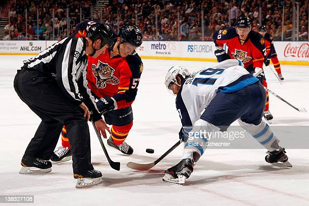 Linesman Steve Barton drops the puck while Marcel Goc of the Florida Panthers faces off against Jim Slater of the Winnipeg Jets at the BankAtlantic...