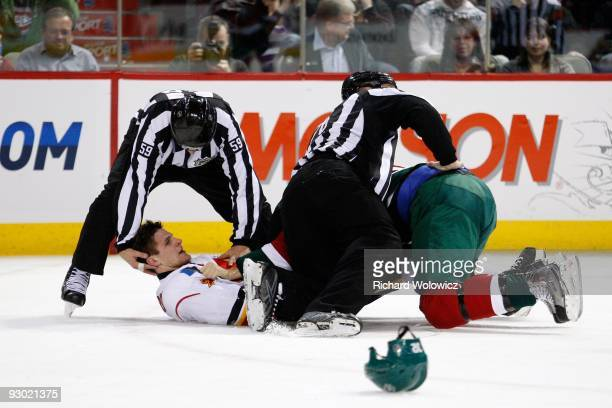Linesman Steve Barton holds up the head of Adam Pardy of the Calgary Flames after a fight with Travis Moen of the Montreal Canadiens during the NHL...