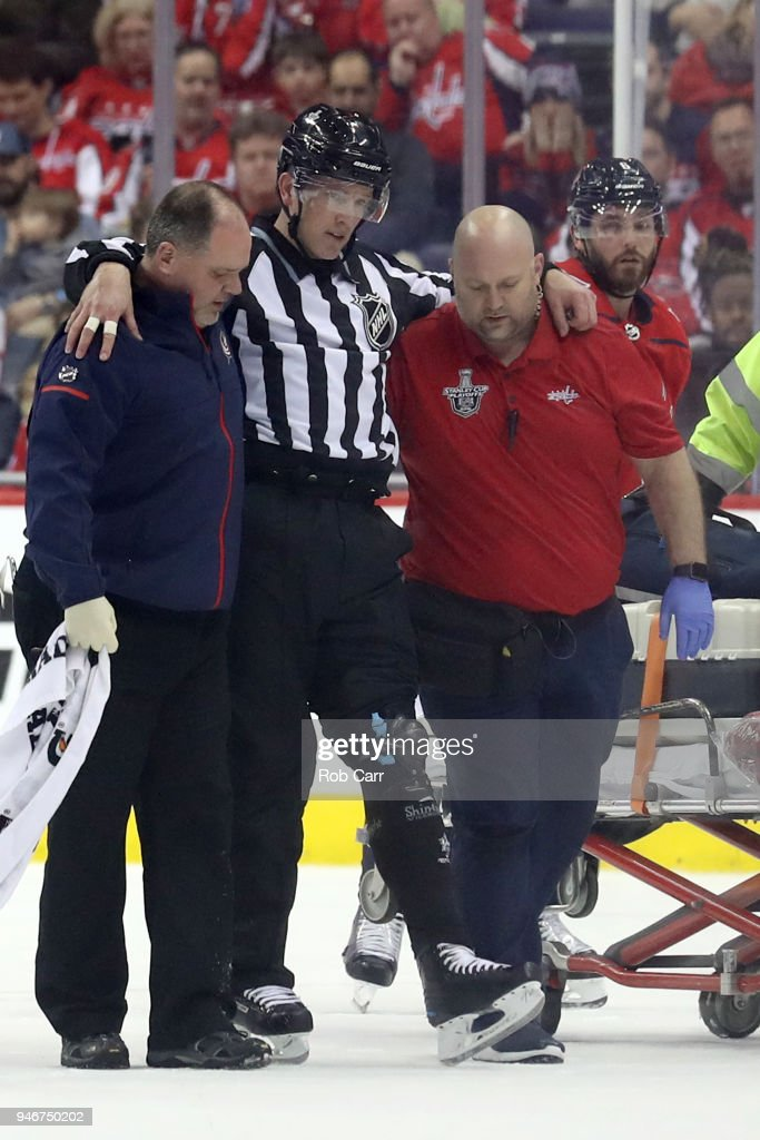 Linesman Steve Barton #59 is helped on the ice after being injured and leaving the game in the second period of the Washington Capitals and Columbus Blue Jackets Game Two of the Eastern Conference First Round during the 2018 NHL Stanley Cup Playoffs at Capital One Arena on April 15, 2018 in Washington, DC.