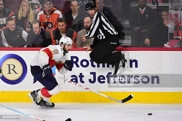 Linesman Steve Barton leaps over the puck being carried by Florida Panthers Defenceman Keith Yandle during a National Hockey League game between the...