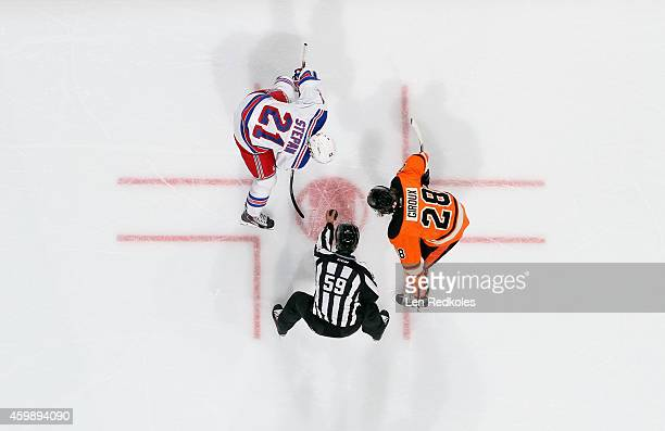 Linesman Steve Barton prepares to drop the puck on a faceoff between Claude Giroux of the Philadelphia Flyers and Derek Stepan of the New York...