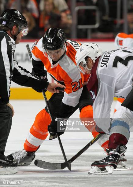 Linesman Steve Barton prepares to drop the puck on a faceoff between Scott Laughton of the Philadelphia Flyers and Carl Soderberg of the Colorado...