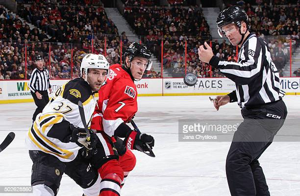 Linesman Steve Barton reacts as the puck flips up following a faceoff between Kyle Turris of the Ottawa Senators and Patrice Bergeron of the Boston...