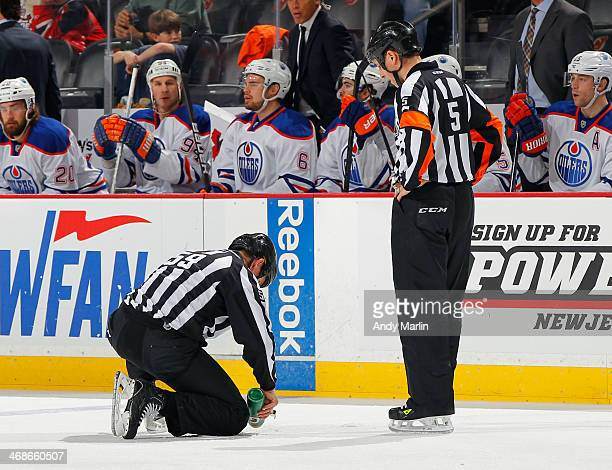 Linesman Steve Barton repairs the ice as referee Chris Rooney looks on during the game between the Edmonton Oilers and the New Jersey Devils at the...