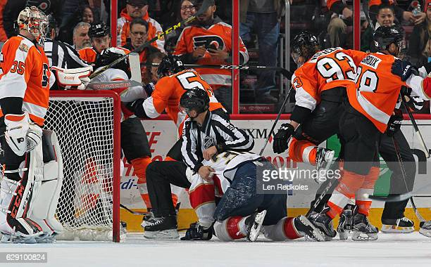 Linesman Steve Barton restrains Jussi Jokinen of the Florida Panthers during a scrum against the Philadelphia Flyers on December 6 2016 at the Wells...