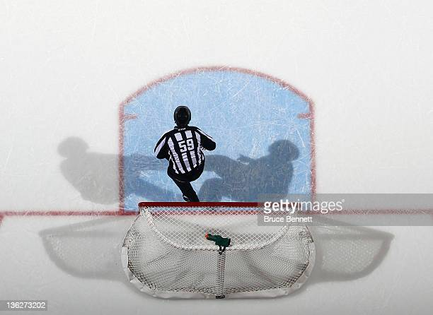 linesman Steve Barton retrieves the puck from the net during the game between the New York Islanders and the Calgary Flames at the Nassau Veterans...