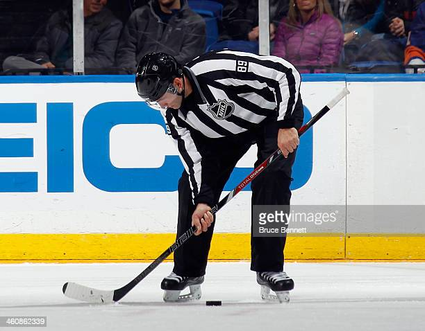 Linesman Steve Miller fixes the ice with a hockey stick during the game between the New York Islanders and the Carolina Hurricanes at the Nassau...