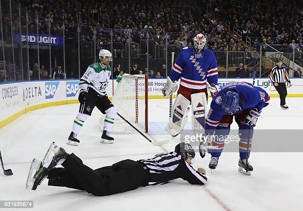 Linesman Tim Nowak is attended to by Mats Zuccarello of the New York Rangers after he gets tripped up during the game against the Dallas Stars at...