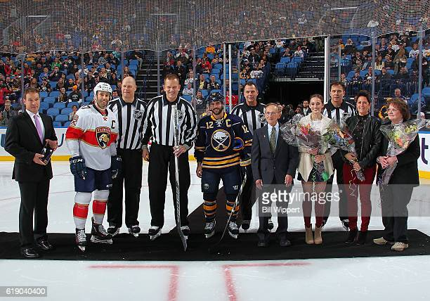 Linesman Tim Nowak is recognized for his 1500th career game by Derek MacKenzie of the Florida Panthers and Brian Gionta of the Buffalo Sabres prior...