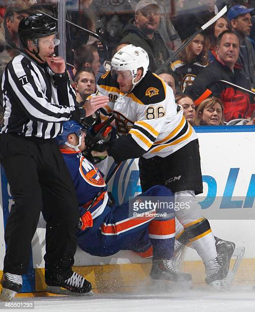 Linesman Tim Nowak tries to blow the whistle as Kevan Miller of the Boston Bruins slams Peter Regin of the New York Islanders with a body check...